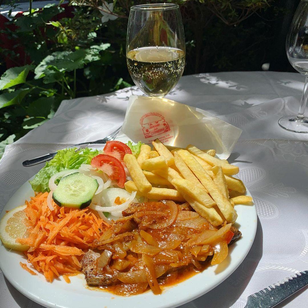 Restauracja Jardim da Carreira w Funchal, danie dnia stek z tuńczyka z cebulą. Każdego dnia można wybrać jedzenie na jakie ma się ochotę jako danie dnia. Cena jedyne 5,50 e. Lampka białego chłodnego wina wskazana wśród promieni słonecznych ogrodu.Zapraszam